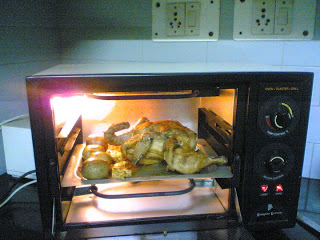 Chicken being roasted with potatoes in the Oven