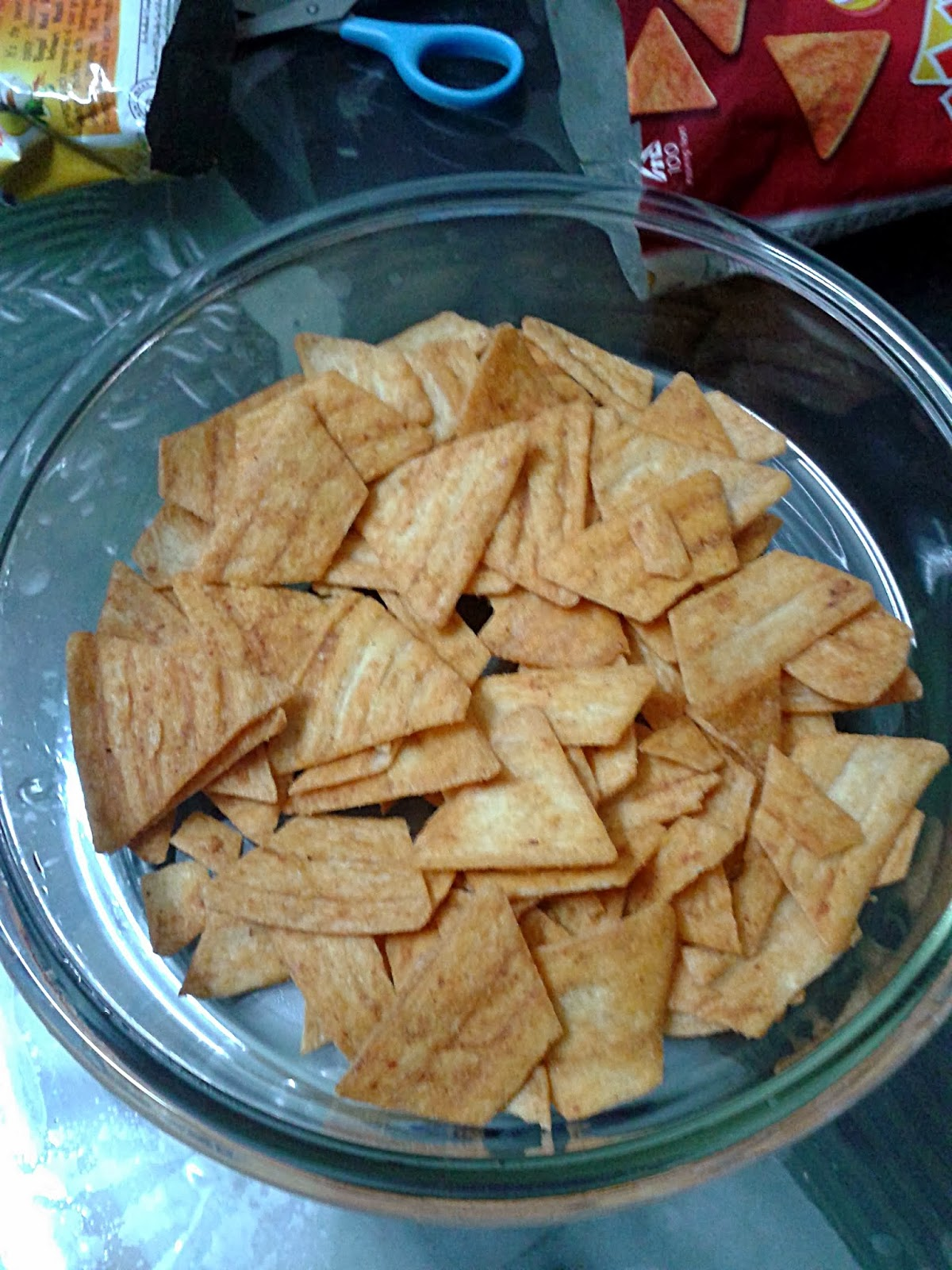 Spread a layer of Corn Chips at the base of a Microwave safe bowl